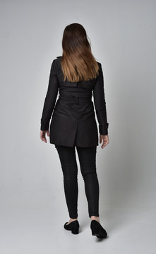 full length portrait of a brunette girl wearing long black coat, standing pose with back to the camera, on grey studio background.