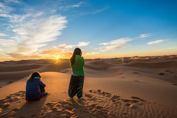 Two women watching a beautiful sunrise over Erg Chebbi sand dunes near Merzouga, Morocco