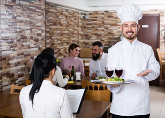 Young man cook welcoming  visitors to restaurant