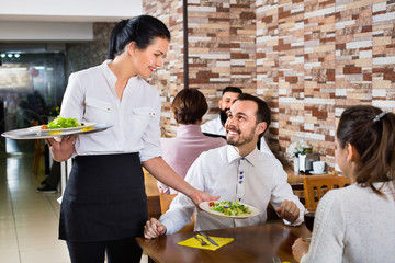 Female waiter bringing order to visitors in country restaurant