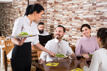 Woman waitress serving meal for cafe guests