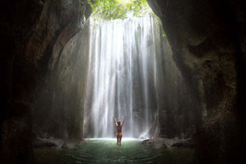 Woman with arms raised to gorgeous scenic epic majestic waterfall in cave with light rays