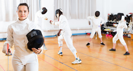 Portrait of smiling sporty young woman with foil at fencing workout