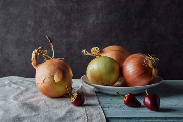 vegetable still life, composition with ripe onions and white dishes on the old table, food ingredients, dark tonality, close-up