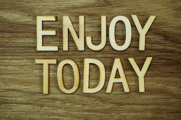 Enjoy Today text message on wooden background