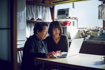 Senior and young woman using laptop together