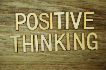 Positive Thinking text message on wooden background