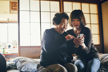 Senior and young woman using smartphone together