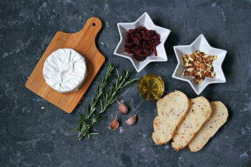 Ingredients for cooking baked camembert: camembert cheese, dried cranberries, fresh rosemary, olive oil, garlic, walnuts, white bread for toasts. Top view, copy space.