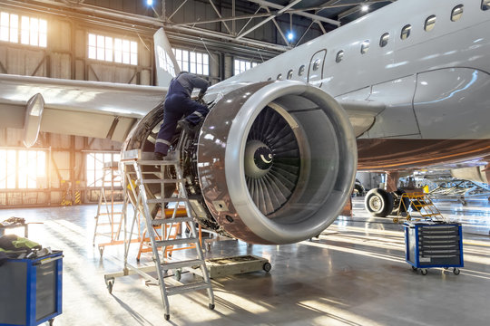 Mechanic specialist repairs the maintenance of engine of a passenger aircraft in a hangar