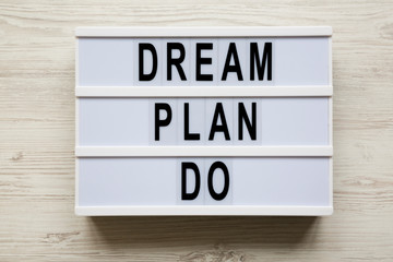 Lightbox with text 'Dream plan do' over white wooden background, top view. Business concept. From above, flat-lay, overhead.