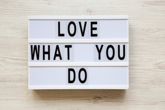 Lightbox with text 'Love what you do' over white wooden surface, top view. Business concept. From above, flat-lay, overhead.