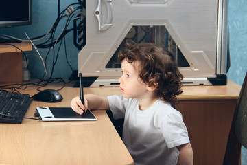Little 2 3 year old baby girl in white clothers draws at the home computer in graphics drawing tablet. The child is holding a pen emotion surprise. Close up