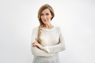 Confident senior woman wearing elegant sweater and long braid crossing arms, smiling. Attractive stylish mature female with green eyes and wrinkles posing at blank wall with copy space for your text