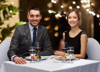 people and leisure concept - smiling couple with food and non-alcoholic red wine at restaurant over festive lights on background
