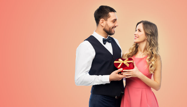 valentines day and people concept - happy couple with gist box in shape of heart over living coral background