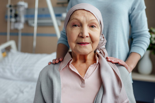 senior woman in kerchief with daughter on background in hospital