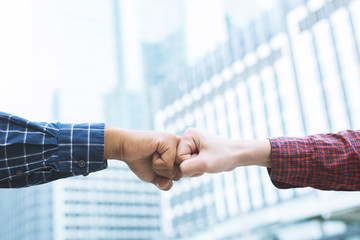 close up image of a fist bump collide agreement. Hands of business man show strength teamwork,  handshake  negotiations finish together after good deal. Business success concept. building background