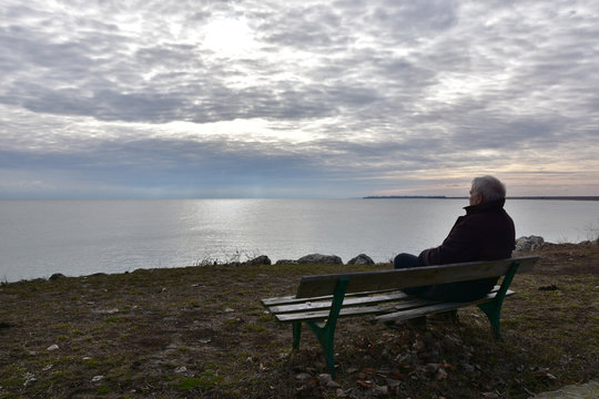 Silhouette of a man over 50 years sitting on an old wooden bench above the see in a cloudy winter day. Senior man quietly watching the see. Nostalgic mood. Duran Kulak, Bulgaria