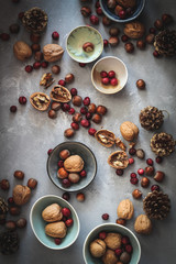 Dark mood flat lay with nuts and dried berries in small bowls