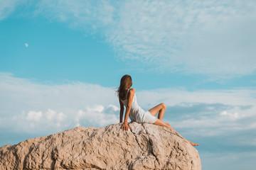 teenager sitzt auf Felsen, Rückansicht