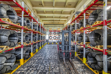 Factory stock wire. Wire spools lie on multi-tiered racks.