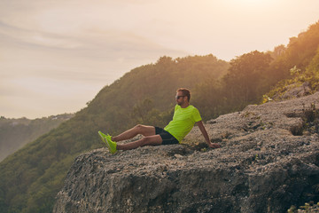 Sportsman watching tropical landscape after workout on a hill.