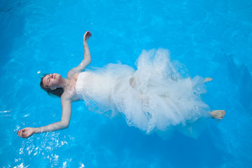 Girl in white dress lying on the water surface