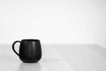Black tea or coffee cap on the white wooden table on white background. Copy space, close up, black and white photo.