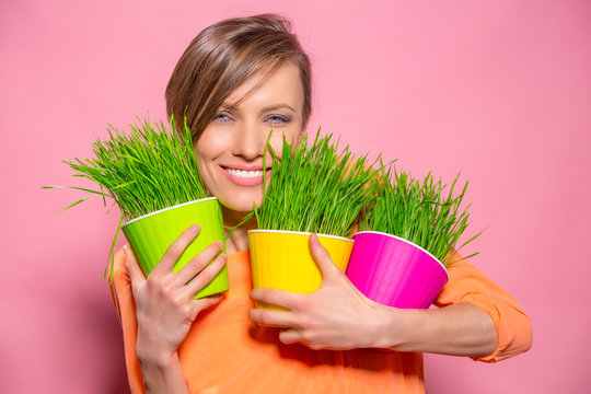 Young lady with wheatgrass in flower pots over brigh pink background