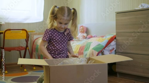 2d4e1188f6d89 Girl opens the parcel from the online store. Child looks in the box ...