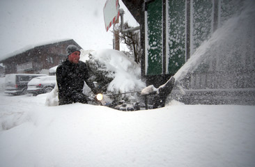 A man uses a snow blower after heavy snowfalls in Schaftlach