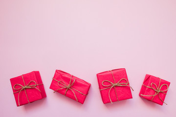 .Red gift box on pink background. February 14 card, Valentine's day. 8 March, International Happy Women's Day. Flat lay, top view, copy space