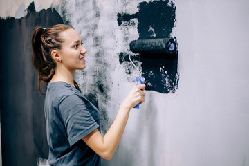 The painter repaints the gray wall in black. Repairs