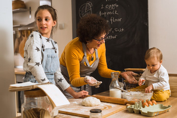 senior woman and her grandchildren baking together in kitchen