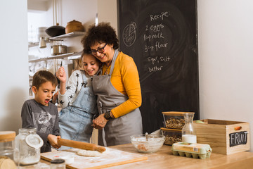 sharing the kitchen responsibilities. senior woman baking together with her grandchildren at home