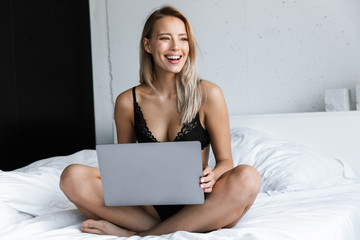 Amazing beautiful young woman in lingerie underwear at morning in bed at home using laptop computer.