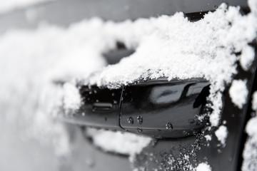 closeup of a doorknob of a car with snow