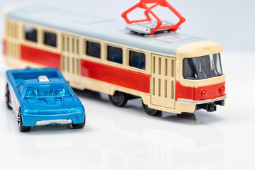 Toy red and yellow tram and toy blue car