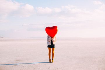 Young Woman Holding Red Heart Shaped Balloon