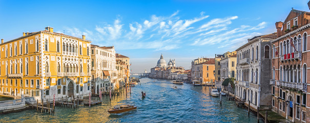 Grand Canal in Venice, Italy. Wide view of the main street panorama of the major street of Venice with motor boats with beautiful picturesque clouds in the sky. Basilica di Santa Maria della Salute.