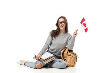 happy female student sitting with canadian flag and notebooks isolated on white