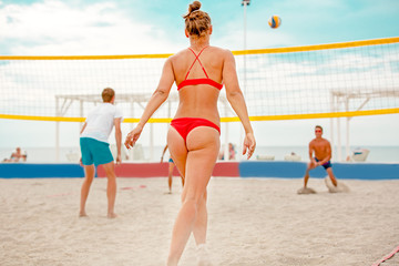 Volleyball beach player is a female athlete volleyball player getting ready to serve the ball on the beach