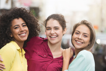 Diverse friends hugging and laughing on the street
