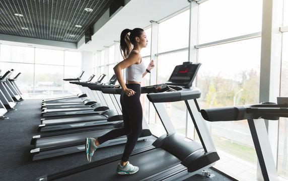 Sports woman training on treadmill near the window