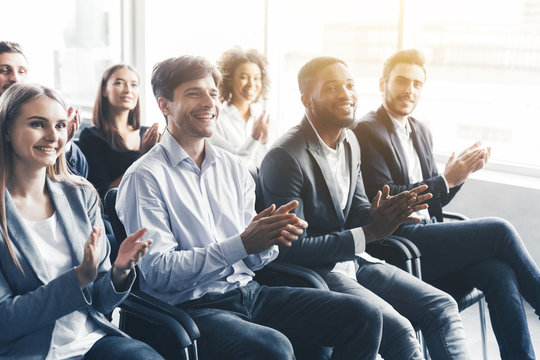 Happy diverse audience applauding at business seminar