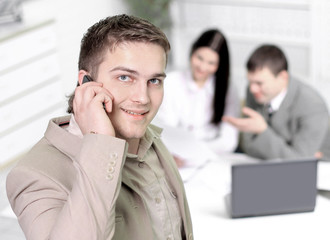 Young smiling businessman calling on phone at office. on the background of the working meeting the business team