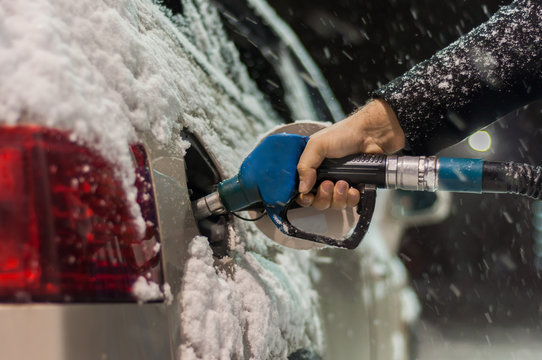 A man in a black coat fills his car at a gas station on a snowy winter evening. Hand holding a blue refueling gun..