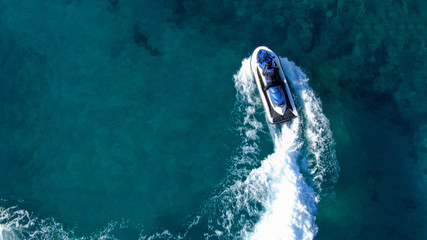 Aerial top view of jet-ski cruising in low speed in mediterranean emerald clear waters