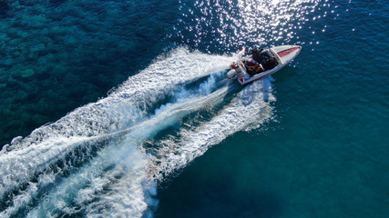 Aerial drone photo of power boat cruising in high speed in deep blue sea